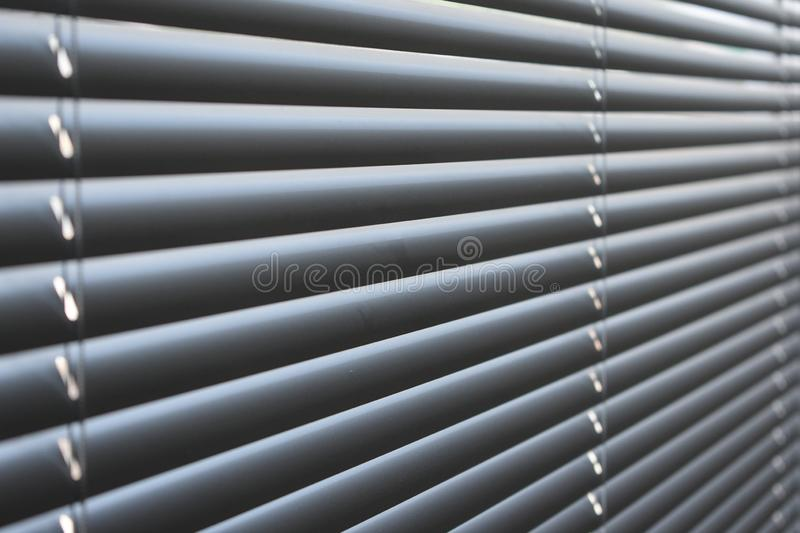 Closed metal blinds, sunlight reflection royalty free stock image