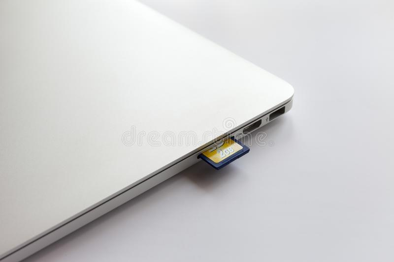 Closed metal laptop on a white table. 8gb sd card inserted into card reader. stock photos