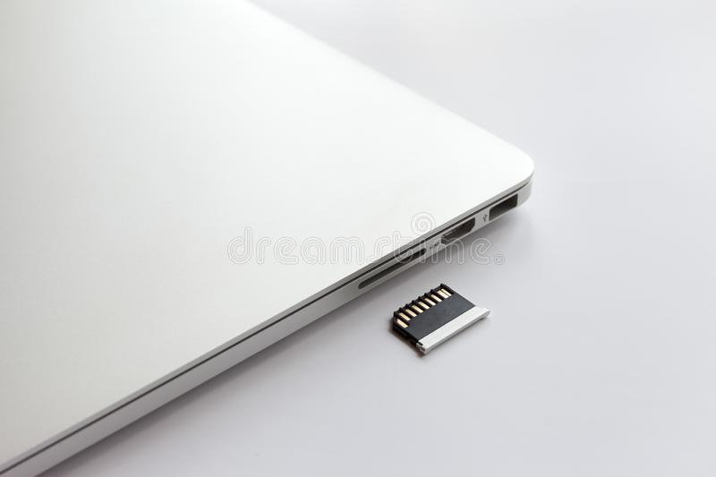 Closed metal laptop on a white table. Near the adapter to the card reader. royalty free stock photography