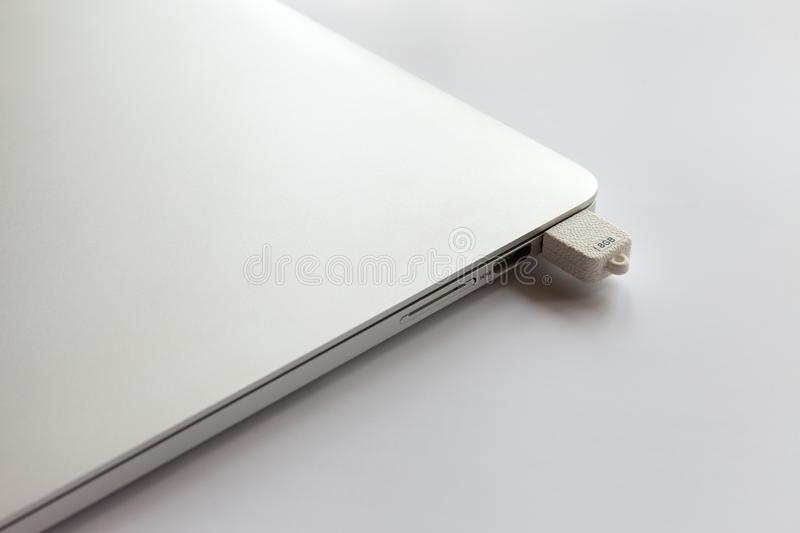 Closed metal laptop on a white table. In the usb connector is inserted 8GB flash drive. royalty free stock photography