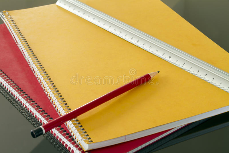 Closed notebooks with pencil and slat. Closed notebooks in yellow and red with pencil and slat royalty free stock photo