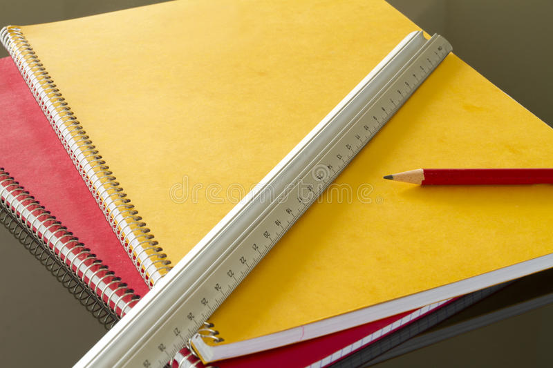 Closed notebooks with pencil and slat. Closed notebooks in yellow and red with pencil and slat royalty free stock images