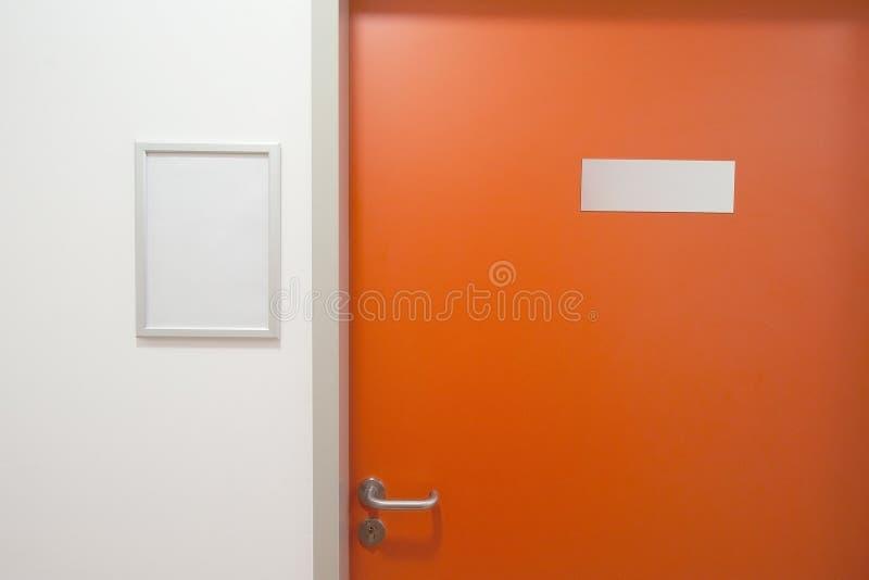 Closed office door. Modern orange door with blank table