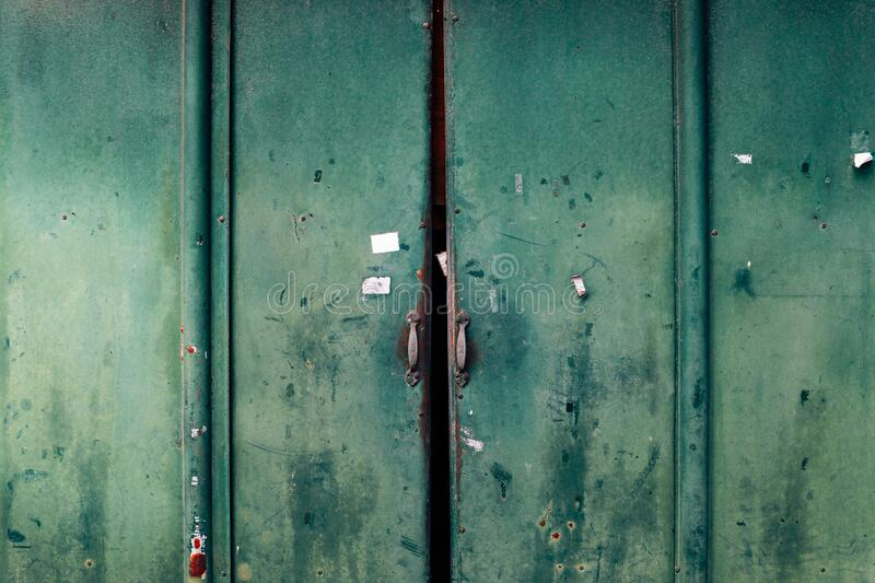 Closed old rusty metal green door. Background royalty free stock photography