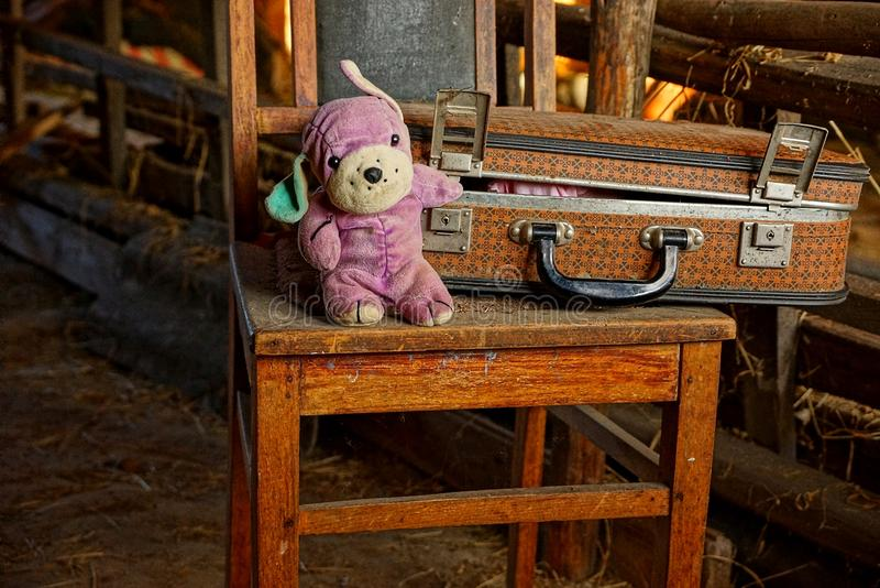 Closed old suitcase with a plush toy stand on an old wooden chair. A children`s toy near an old brown suitcase on a wooden chair in the house stock images
