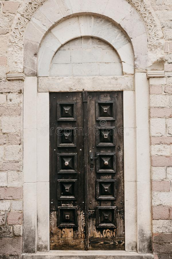 A closed old wooden door at the entrance to the building stock photos