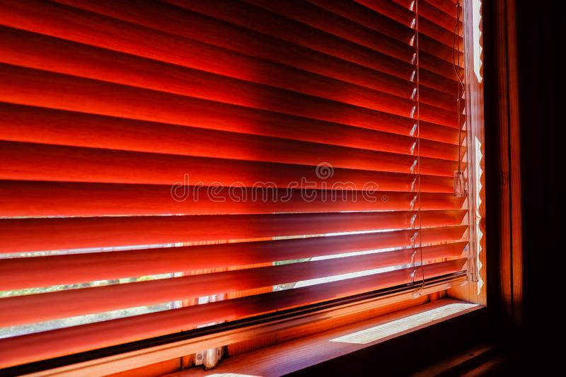 Closed orange plastic blinds with sunlight in the morning. window with blinds. Interior design of living room with. Window horizontal blinds royalty free stock photo