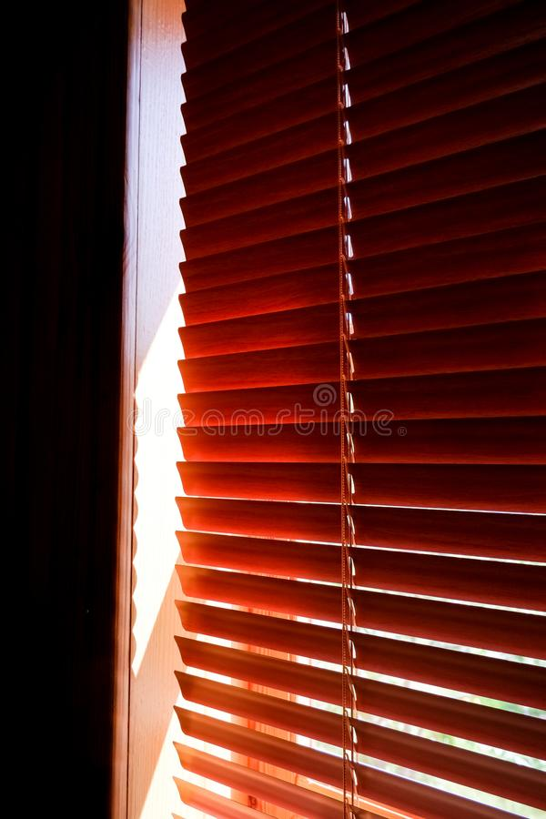 Closed orange plastic blinds with sunlight in the morning. window with blinds. Interior design of living room with. Window horizontal blinds stock photos