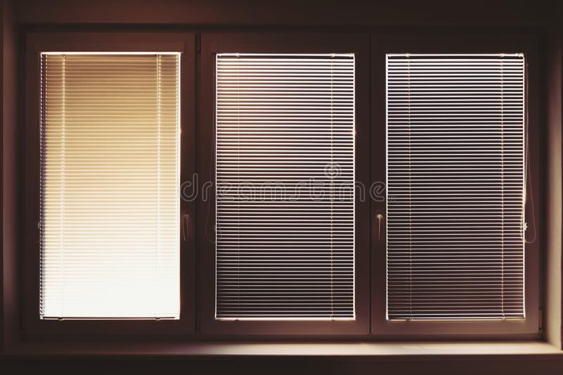 Closed plastic window on sunny day with horizontal plastic blinds. Retro vintage look stock photography