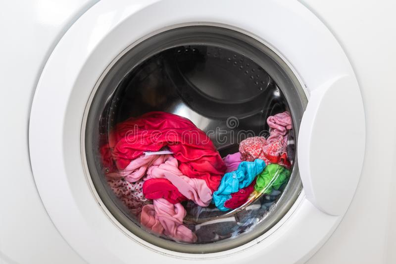 Closed round washing machine door with rotating garments inside. Focus in the center of dirty laundry and washing. Machine on the frame royalty free stock photo