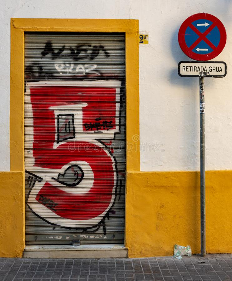 Closed shutters with giant number five graffiti embalzoned on the front stock photos
