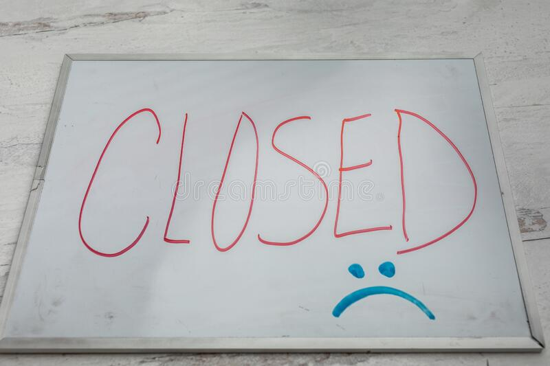 Closed sign on dry erase board with a sad face economic closure royalty free stock photos