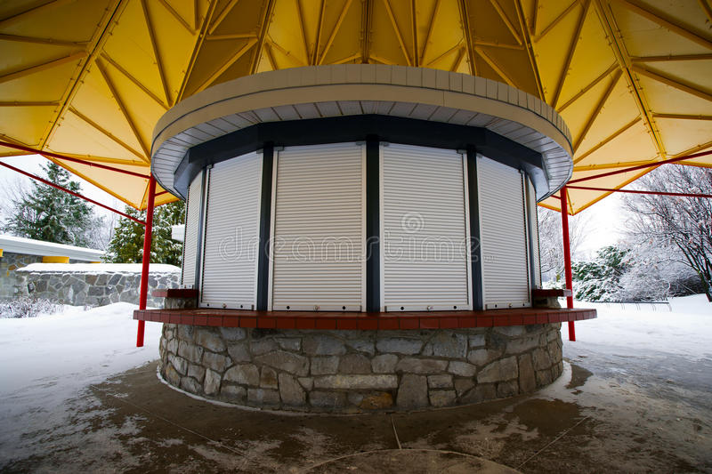 Closed Small Circular Kiosk. A small, closed and shuttered circular kiosk in a municipal park in winter stock photography