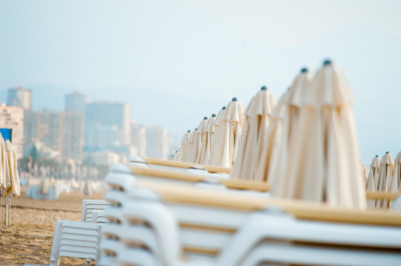 Closed umbrellas on the beach on the morning royalty free stock image