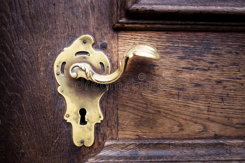 Closed up - Ancient golden keyhole for security on wooden door stock photos