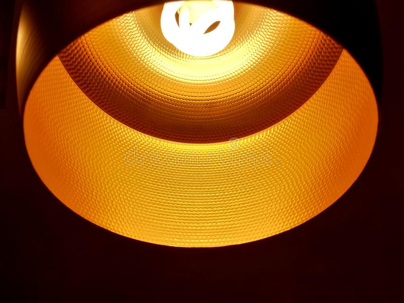 Closed up of black orange ceiling lamp with energy saving fluorescent light bulb stock photos