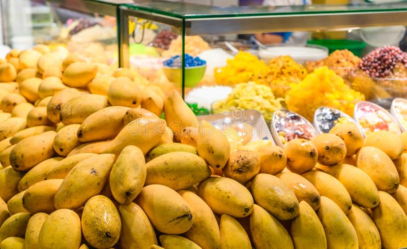 Closed up a bunch of mangoes with colorful thai sweet dessert in background on street market. Ripe mango at street food shop for. Thai dessert mango and sticky royalty free stock images