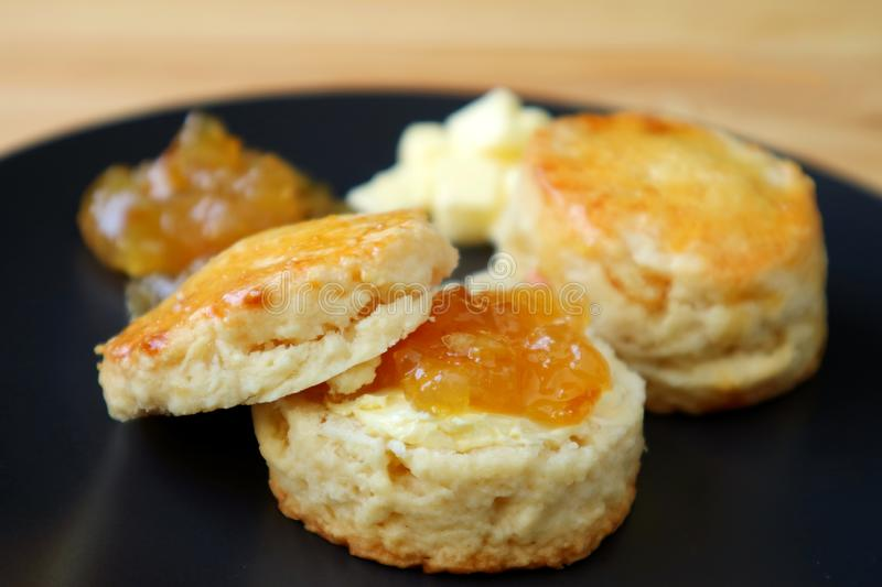 Closed Up Candied Orange Peel Scones with Marmalade Jam and Butter Served on a Black Plate stock photos