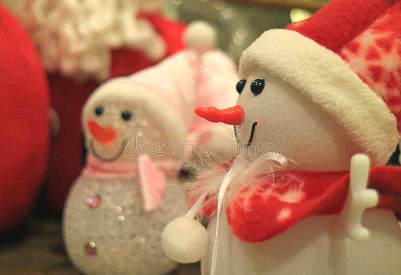 Closed up a cute snowman doll in red outfit with blurred another snowman in background royalty free stock images