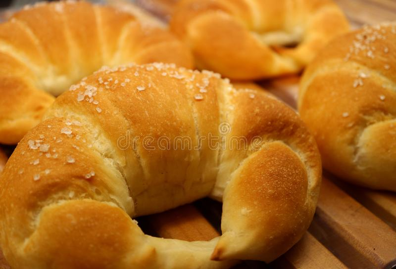 Closed up fresh baked sugar coated croissants on the wooden tray stock images
