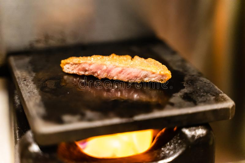 Closed up of fried pork meat grill on hot stone on small fireplace, very delicious traditional japanese food stock photos