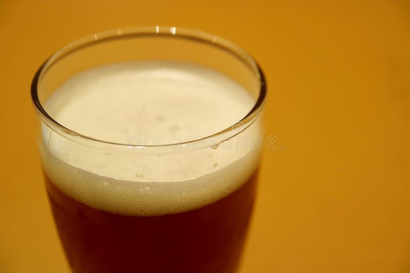 Closed Up a Glass of Dark German Lager Beer on the Table royalty free stock photography