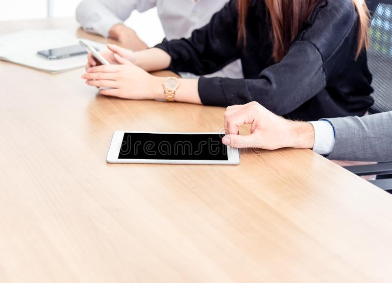 Closed up hands of business people with tablet pc with blank screen while sitting at the wooden table work in meeting room. stock images