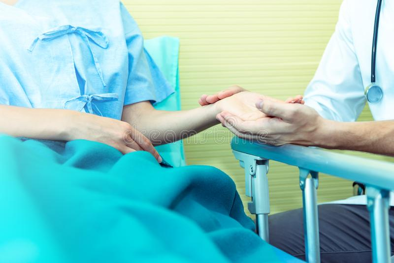 Closed up of Hands of doctor man reassuring woman patient on bed in  hospital .Professional medical doctor comforting patient at. Consulting room. Medical royalty free stock image