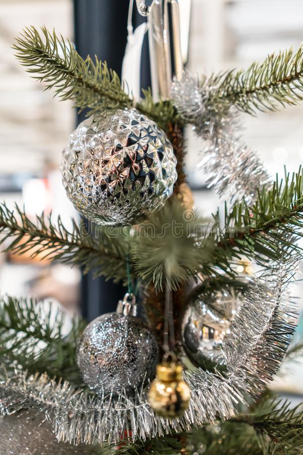 Closed up hanging shiny patterned silver ball, tinsel and ornaments on green christmas tree stock photo