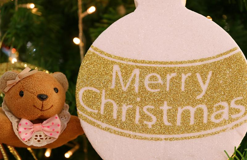 Closed up Little Teddy Bear with Gold and White Merry Christmas Ornament. Blurred Lighting Background stock image