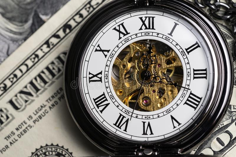 Closed up of mechanical vintage pocket watch on US dollar banknotes background as time for invest concept stock photography