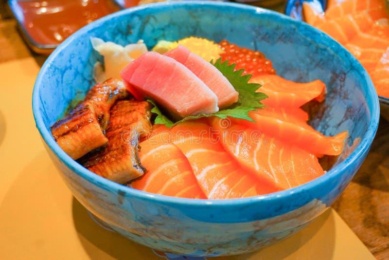 Closed up mix fresh raw secfood on topped rice bowl donburi. Japanese food stock photography