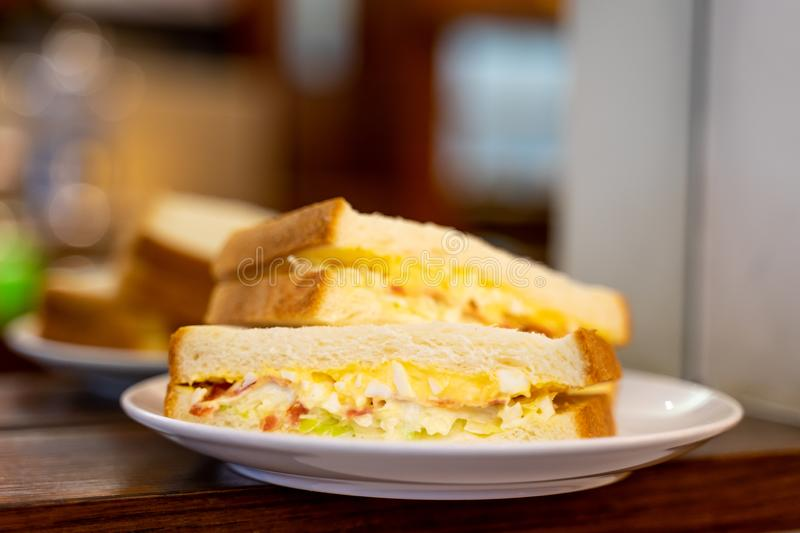 Closed up of morning sandwiches with egg, ham and vegetable on white dish in coffee shop.  stock photography