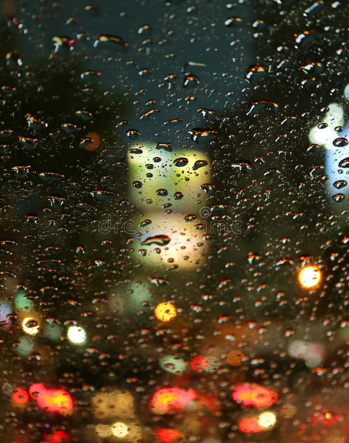 Closed up raindrops on the car windshield during a driving on the urban street at night. For Background royalty free stock images