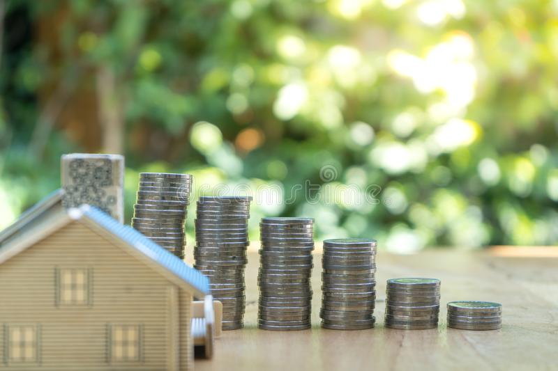 Closed up shot of small house with Coin stacks on green background. stock images