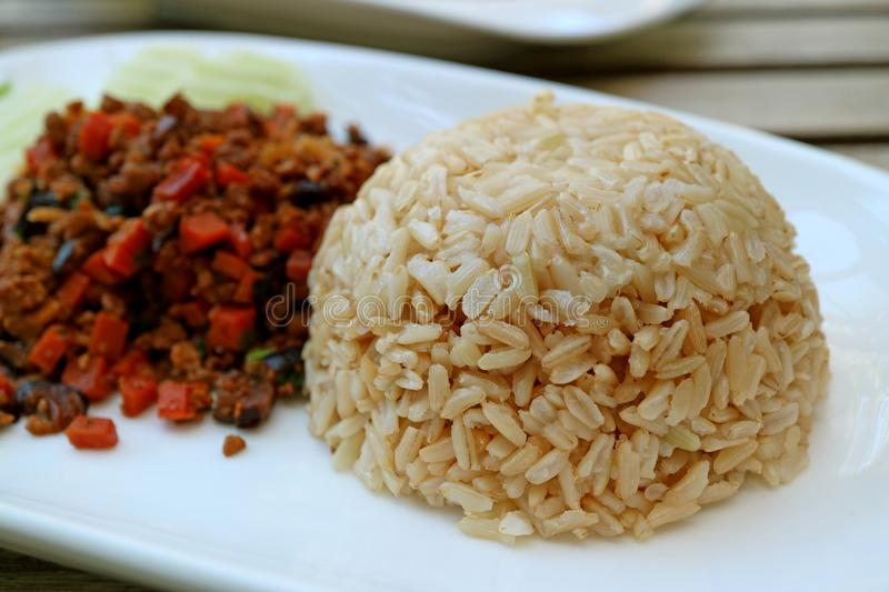 Closed Up Steamed Thai Brown Jasmine Rice with Blurred Sauteed Vegetables Served on White Plate royalty free stock photos