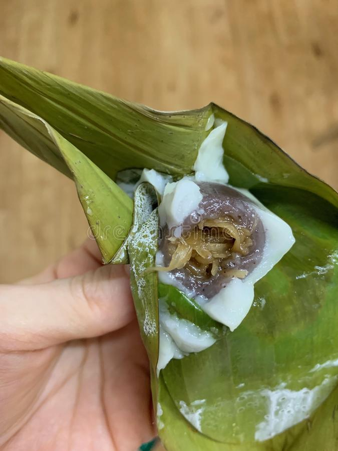 The closed up of sweets stuffed with traditional Thai desserts made from flour and coconut on the banana leaf on hands of women stock photo