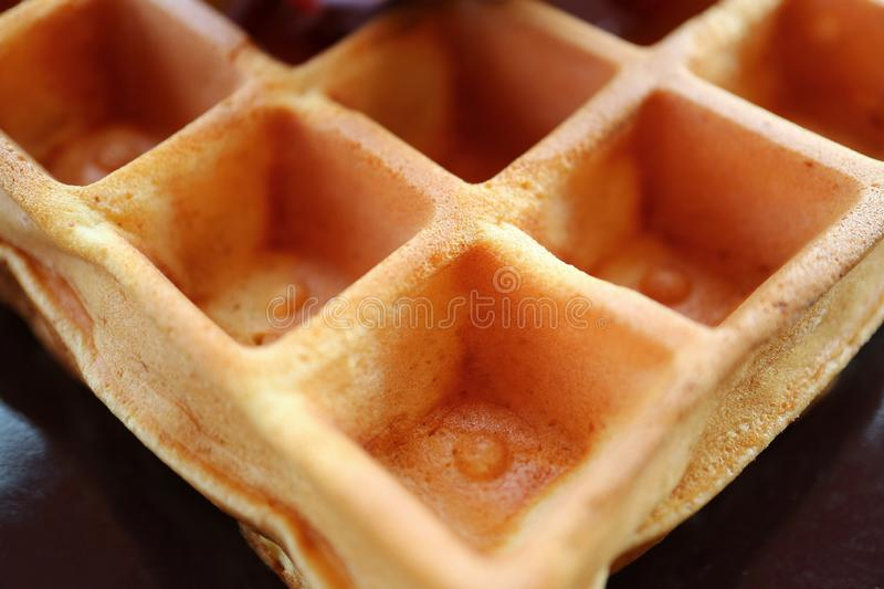 Closed Up the Texture of a Tasty Square Shaped Waffle on a Black Plate royalty free stock photos