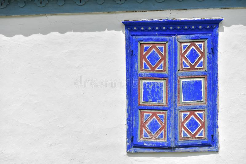 Closed vintage blue and red window on white wall of old traditional house in romania royalty free stock photography