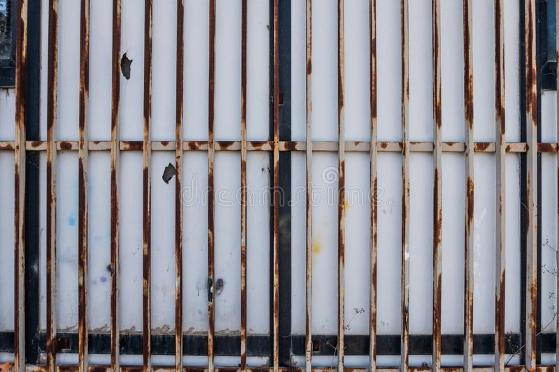 Closed white bars rusty metallic gate detail. Facade on a sunny day stock image