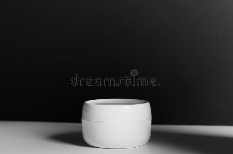 Closed white jar of face cream on a black background with dark shadow. Cosmetic moisturizing product stock photo