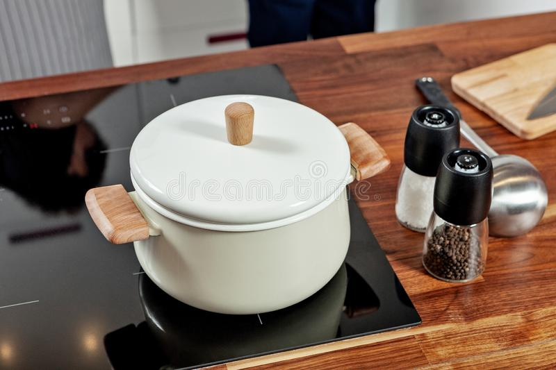 Closed white saucepan with wood pens on the black stove and glass spice mills with papper and salt on the wood table in the. Kitchen room royalty free stock photo