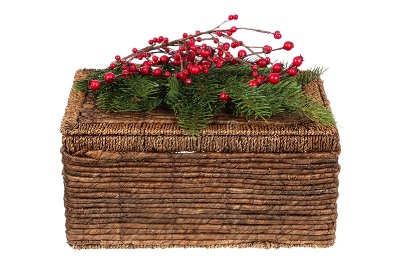 Closed wicker picnic basket decorated for Christmas with pine twigs and holly berries ornaments isolated on white background stock image