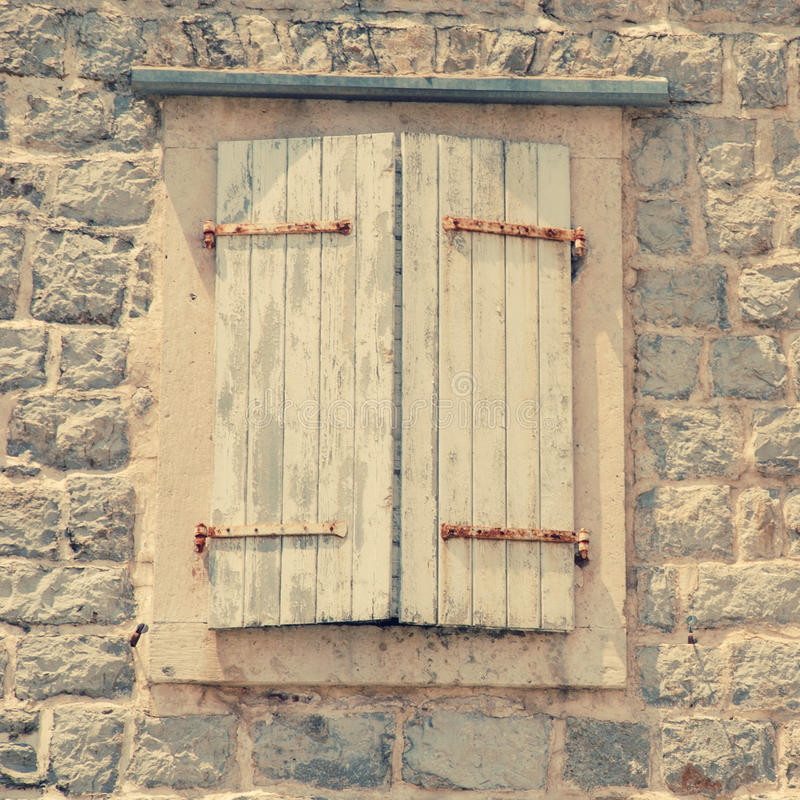 Closed window with shutters in old rough stone wall of ancient i royalty free stock photography