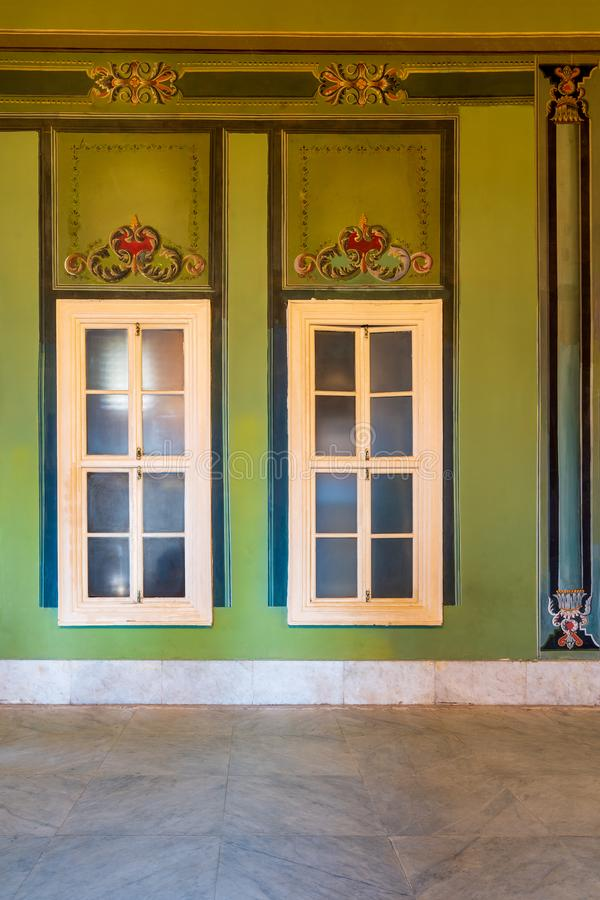 Closed windows and beautiful elegant carved frames on green wall with ornate border and marble floor. Two narrow closed windows and beautiful elegant carved stock photography
