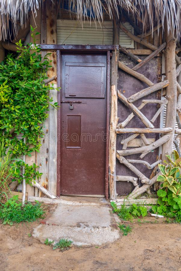Closed wooden brown grunge door and thatch roof, surrounded by green bushes royalty free stock photo