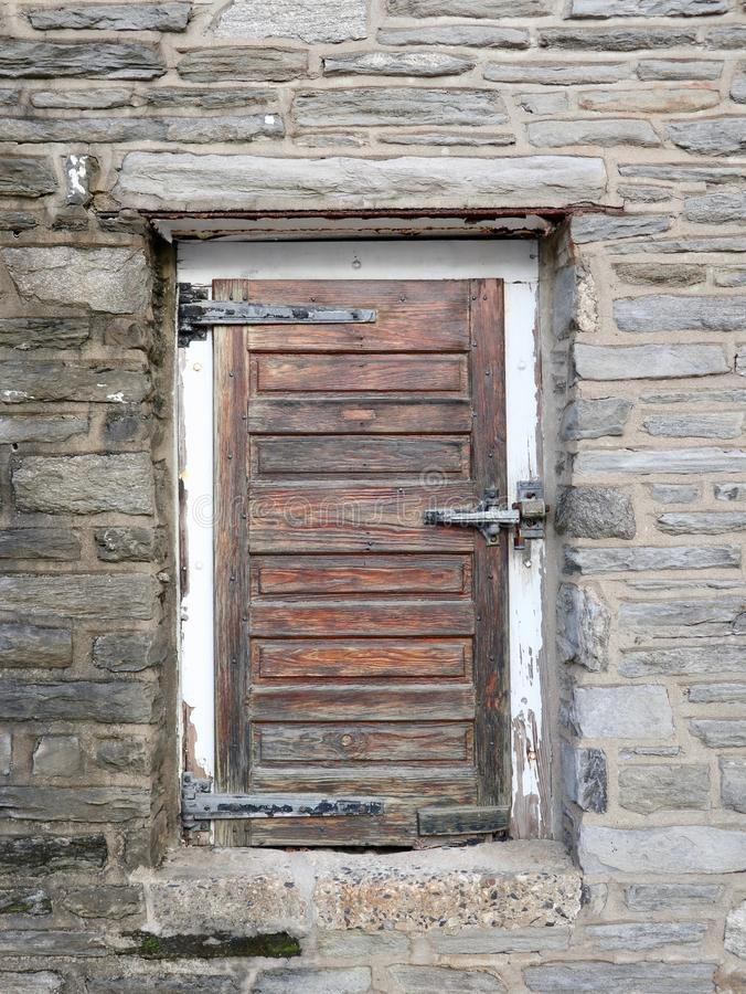 Old Rustic Wood Door in Stone Wall royalty free stock photography