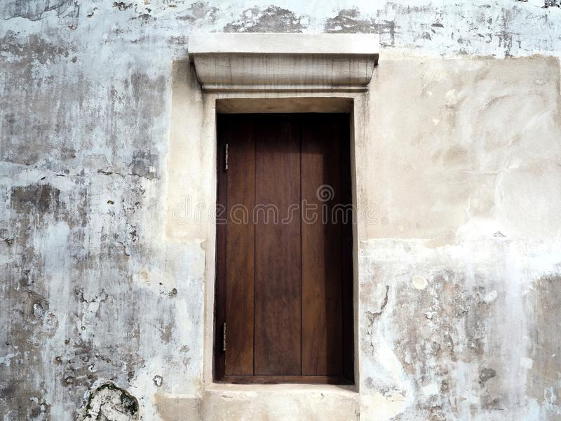 Closed Wooden Window on the Old White Concrete Wall royalty free stock photos