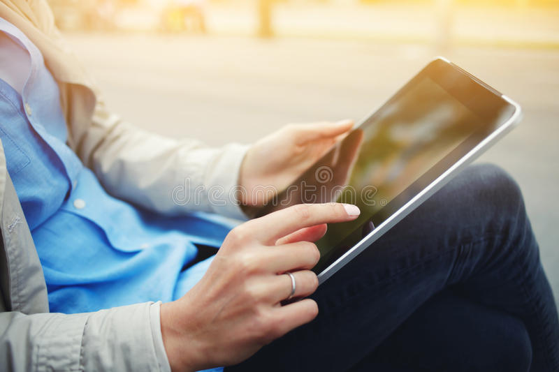 Closely of hipster girl is using touch screen digital tablet while sitting in the park outdoors royalty free stock photos