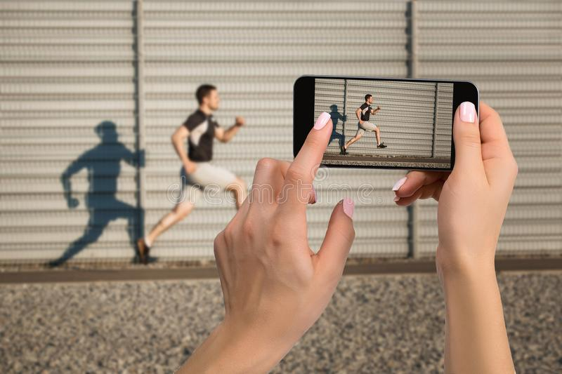 Closely image of female hands holding mobile phone with photo camera mode on the screen. Cropped image of athletic man. Running along beautiful grey wall royalty free stock photo